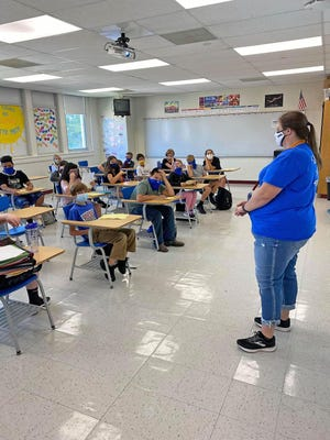 Laura Speed Elliott Middle School teacher Jennifer Overfield welcomes students back Monday for the first day of school. Schools are facing a different landscape of instruction this year due to the ongoing COVID-19 pandemic, with many requiring mask usage by students and staff alike.