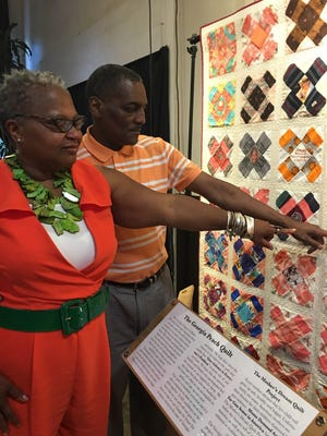 Linda Wilder Bryan with husband, Lawrence Bryan III,  with blanket that Moms Demand Action had tavel the state to the  Capitol depicting lives of sons and daughters killed in acts of violence. A picture are pieces of cloth from sons that mothers contributed and were made into a quilt