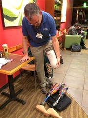 Dave Dunville demonstrates how he puts on his prosthetic leg. He made the decision to have his left leg removed after suffering injuries in a 1999 fall.