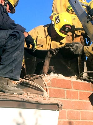 Firefighters work to free Genoveva Nunez-Figueroa from a chimney after she became stuck trying to enter a home in Thousand Oaks, Calif.