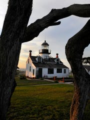 The 1,000-watt lamp at Point Pinos Lighthouse sits 89 feet above sea level in Pacific Grove, where Monterey Cypress frame the historic building.