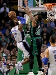 Celtics guard Marcus Smart defends a shot from Magic forward Jonathon Simmons on Friday.