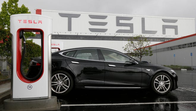 A car is parked at a Tesla charging station outside of the Tesla factory in Fremont, Calif.