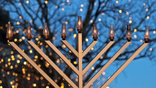 Set against Fort Collins' downtown holiday lights, the celebratory giant Menorah shines after the 11th annual Menorah Lighting and Chanukah Celebration on Sunday, Dec. 13, 2015 in Old Town Fort Collins.