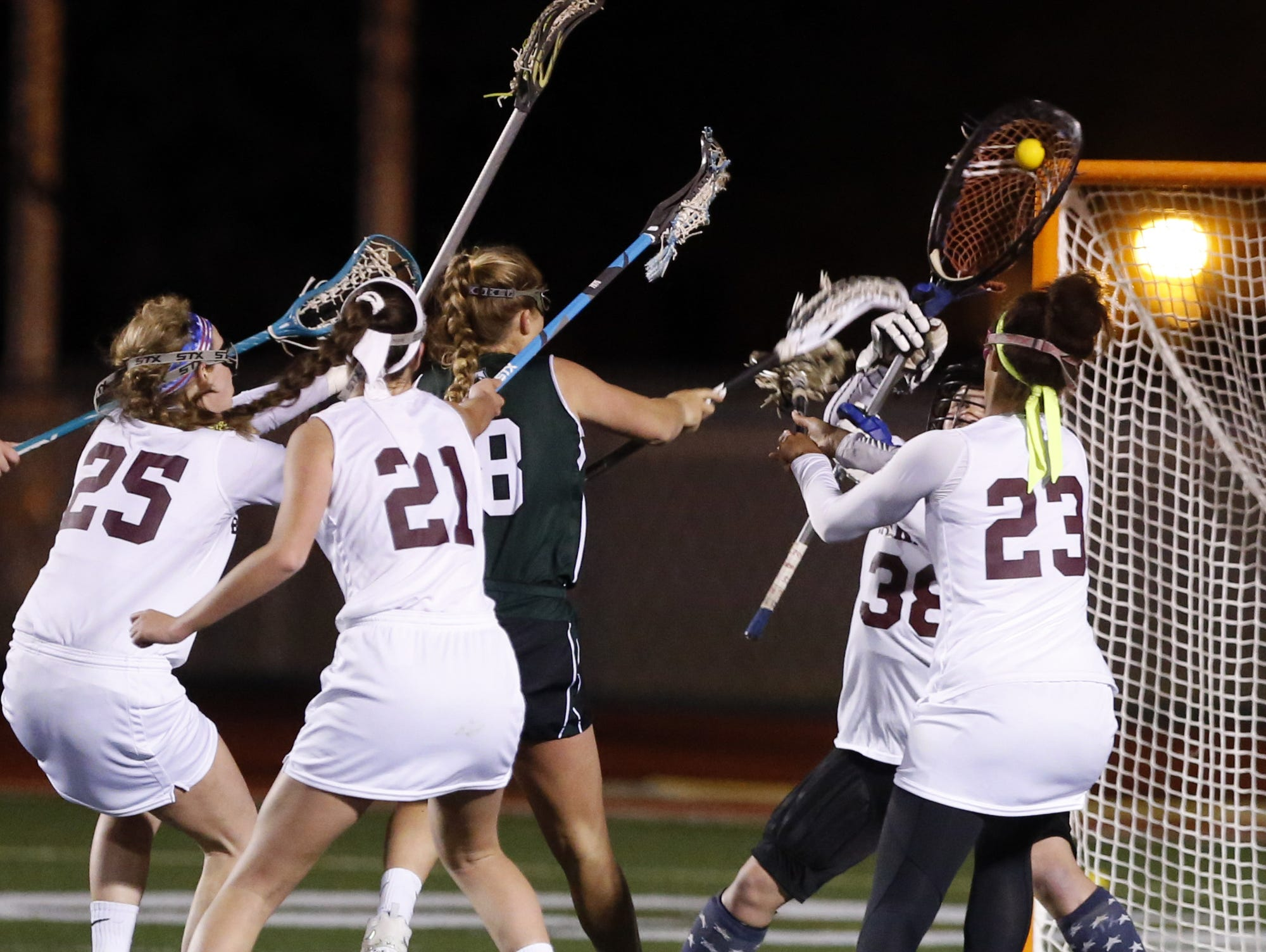 Caravel goalkeeper Hannah Seamans (38) makes a save on Archmere's Sydney Yanick's point blank shot in the final minutes Caravel's home win, 11-9.