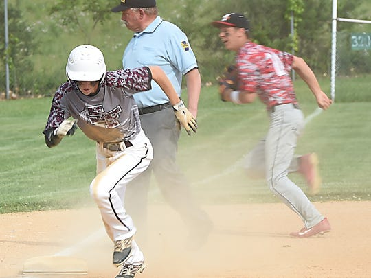 Southern Fulton Zach Clark, 8, scrambles from third base to score a run after a wild throw last year during the District 5-A baseball championship against Meyersdale.