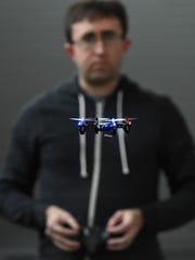 Prof. Richard Kelley of the UNR engineering department demonstrates a tiny drone Wednesday. He says beginners will find the best success with the itsy-bitsy models, moving to bigger drones once they get used to piloting.