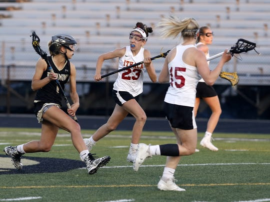 Kelsey Simmons of Corning moves the ball up the field as Quinn Howe of Ithaca defends May 23 during the Section 4 Class A girls lacrosse championship game at Corning Memorial Stadium.
