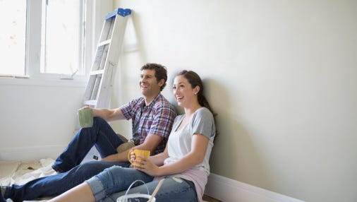 Happy couple drinking coffee on paint drop cloth