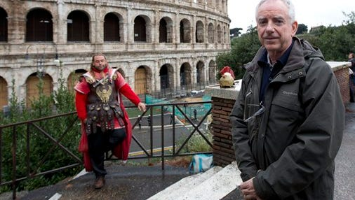 Archaeologist Daniele Manacorda poses in front of Rome's Colosseum Friday. The archaeologist's proposal to return the Colosseum's storied arena to its original state, when gladiators sparred with lion, has sparked a lively debate over appropriate uses of the monument that symbolizes the glories of ancient Rome. Critics have fretted that the Colosseum would be turned into a venue for events like rock concerts, viewed as both unbefitting its stature as an ancient wonder.