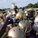 Holy Trinity football players rally at the end of a drill.