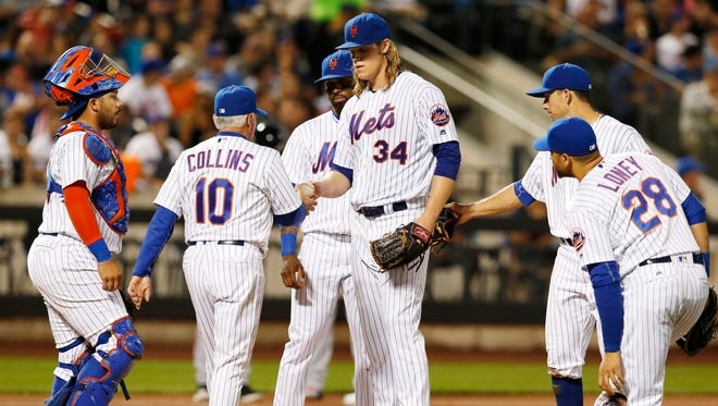 New York Mets' manager Terry Collins (10) takes the ball from Mets' starting pitcher Noah Syndergaard (34) during the fourth inning of a baseball game against the Atlanta Braves, Monday, Sept. 19, 2016, in New York.