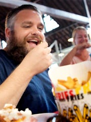 Downtown Inc CEO Silas Chamberlin samples fries at J.R.'s Fries at Central Market during Chamberlin's quest to eat french fries at 27 different downtown York restaurants on National French Fry Day Friday, July 13, 2018. J.R.'s was the fourth stop on the Fantastic French Fry Frenzy tour. Bill Kalina photo