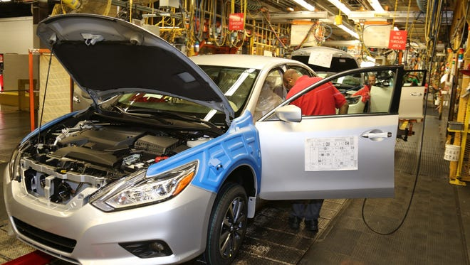 A worker at the Smyrna Vehicle Production Plant works on the updated 2016 Nissan Altima, which began production Monday morning.