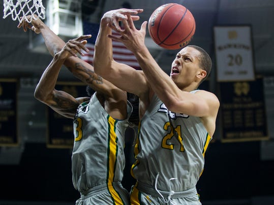FILE - In this Dec. 21, 2017, file photo, Southeastern Louisiana University's James Currington, left, and Jordan Capps (21) fight for a loose ball during an NCAA college basketball game against Notre Dame in South Bend, Ind. The sight of Southeastern Louisiana starter James Currington recuperating from a bullet wound suffered in a shootout near student housing has provided the Lions with a new perspective on their program's best basketball season in more than a decade. Regardless of how the Southland Conference's top seed fares this postseason, the Lions can be grateful no one was killed when some of their players wound up in the midst of another episode of gun violence on a school campus a few weeks ago. (Michael Caterina/South Bend Tribune via AP, File)