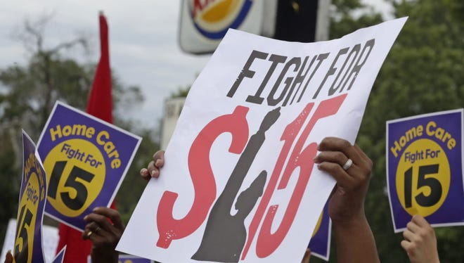 Protesters participate in a rally to raise minimum wage in Chicago, Ill.