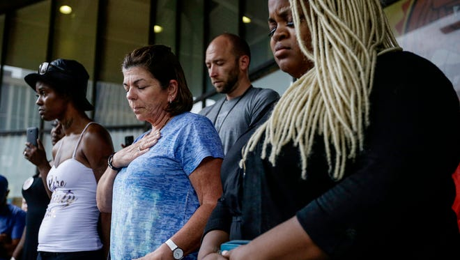 Katie Tyson (left), Peggy Meyer (middle), and Ashley Thomas during a prayer at the Justice for Aaron Bailey rally at City Market on Friday, June 30, 2017.