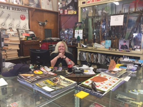 Torrey Harris, owner of Condor Gun Shop in Desert Hot Springs, behind her desk on Thursday, June 30. Harris does not believe the gun laws passed today will prevent any crime in California.