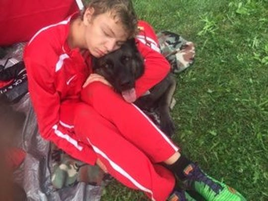 Davenport West's Tyler Gerdts and his service dog, Hugo, cuddle after the first cross country meet of the season at Cedar Rapids Prairie on Saturday, Aug. 27, 2016.