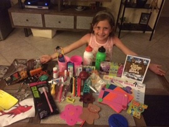 Jaycee Mead, 7, proudly shows her treats from the 2016