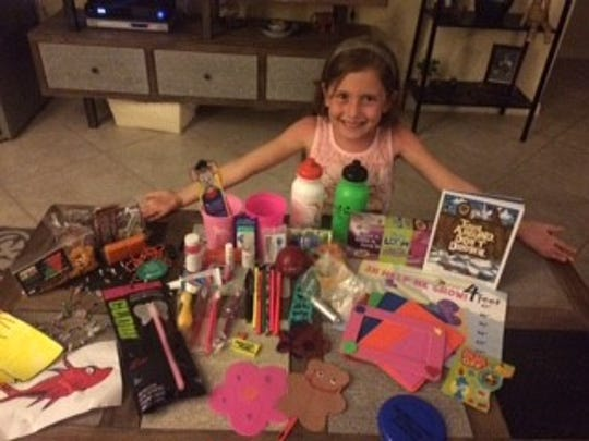 Jaycee Mead, 7, proudly shows her treats from the 2016 Family Fun Fair, hosted by the Early Learning Coalition of St. Lucie County.