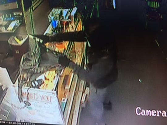 Surveillance photo from the armed robbery of the Meemos Wireless Store on West 70th Street.