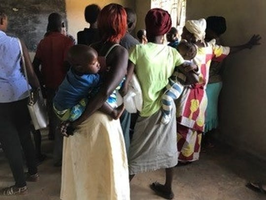 Women wait for mosquito nets to protect their families from malaria.