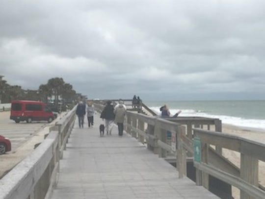 Walkers brave the chilly weather Monday at Conn Beach