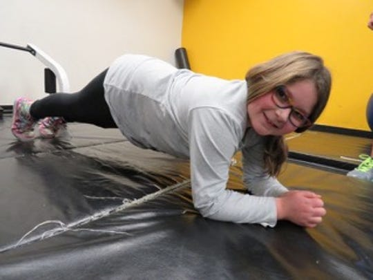 "Nine-year-old Jenna Kanfer works on her ""plank"" position, during her personal training session at the Birmingham Family YMCA."