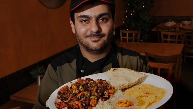 Mike Tokadutian, manage at Rokabab Mediterranean Grill, displays Chicken Shawarma, marinated mix of chopped white and dark chicken with mediterranean spices.