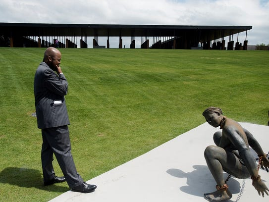 Duane Rankin looks a sculpture depicting slaves at