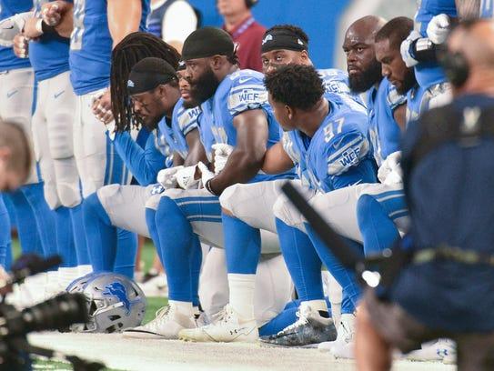 Detroit Lions players kneel.