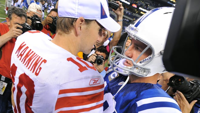 Colts quarterback Peyton Manning talks with brother and Giants quarterback Eli Manning after a Sept. 19, 2010  game at Lucas Oil Stadium. The Colts won 38-14.