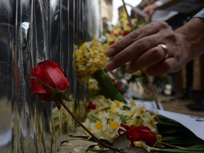 Afghans place flowers Jan. 19 as they pay tribute to the victims of an attack two days earlier, in front of a Kabul restaurant. Twenty-one people, including 13 foreigners, died in the suicide bombing and gunfire.