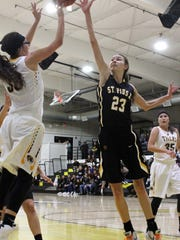 Alamogordo's Faith Silva, left, puts up a shot while being guarded by St. Pius' Arianna Martinez.