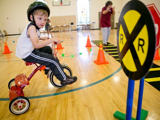 Logan Krohn, 4, goes through the Safety City course to learn about the rules of the road Tuesday at First Presbyterian Church in Marshfield.