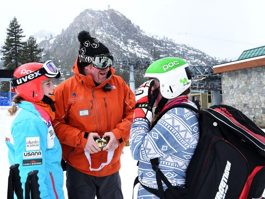 """Teams Program Director Todd """"TK"""" Kelly, middle, interacts with his daughter and team member Kate Kelly, right, at Squaw Valley Ski Area near Truckee, Calif. on Jan. 16, 2015. Fellow racer Georgia Sege is seen on the left."""