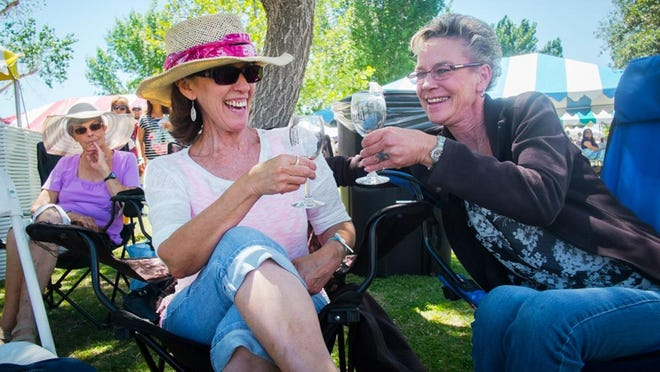 Jett Loe--Sun-News Sylvia Sweat and Lyntha Masterson toast after finishing glasses of wine at the La Viña Winery's annual Spring Wine Festival in Anthony, New Mexico on Saturday. Both drove from Las Cruces for the event; it was Sweat's 10th year coming and Masterson's third. The festival has over 20 wines available for tasting and purchase. In addition to wine there are activities for children and vendors selling a wide variety of food and handicrafts.