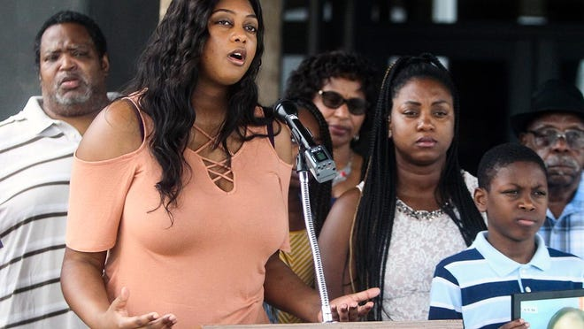 Lakeshia Craft, left, stands next to her sister Torneshia Craft, right center, and shares information about her mother Sharon Selman, who was killed in Pflugerville on March 31. The family is searching is still searching for answers in the unsolved case.