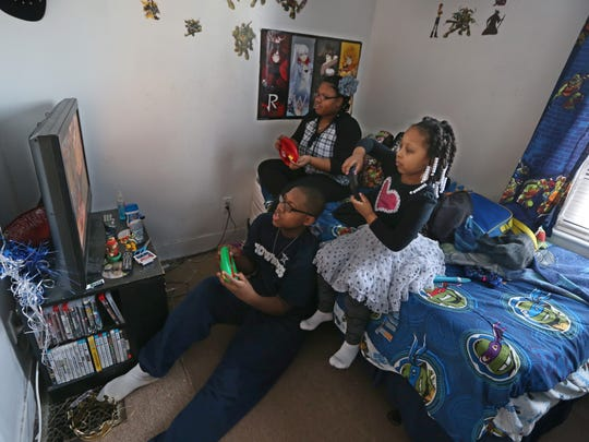 Mieisha Grant's three children Roemello McMillan, seated on floor, Mi'Andrea McMillan, left, and Giavanna McMillan, right, play video games in Roemello's bedroom after they finished their homework at their Rochester home, Monday, March 26, 2018.   All three kids have disabilities.
