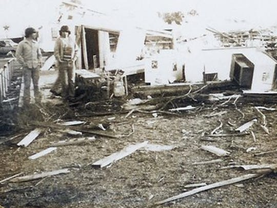 Men examine the remains of businesses destroyed by