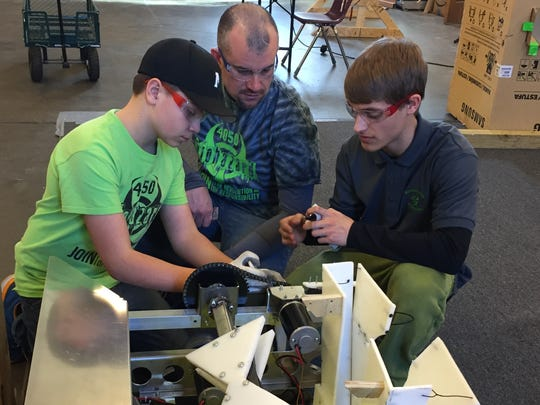 4-H Robotics Club members, left to right,  Seth Young, mentor Troy Young and Chad Beaty work on a robot similar to one the club will enter in 2017 robotic competition this weekend.
