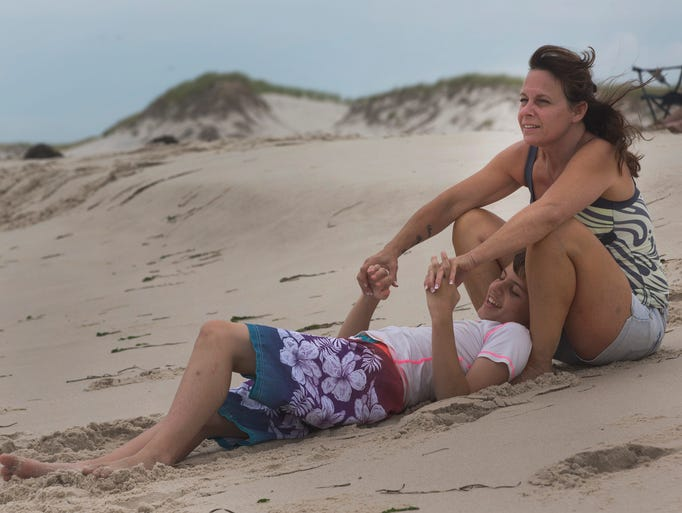Joanne Heer and son Andrew, 13, who has autism relax on the beach after lunch. They are from Middletown. Special Needs kids get their Day at the Beach at Island Beach State Park on August 12, 2014. Peter Ackerman/Asbury Park Press
