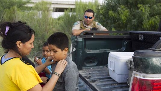 Two Honduran women and two young children wait after being apprehended by game wardens in Mission, Texas, in June.