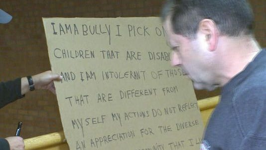 "A judge ordered Edmond Aviv, right, to hold a sign ""I am a bully."""
