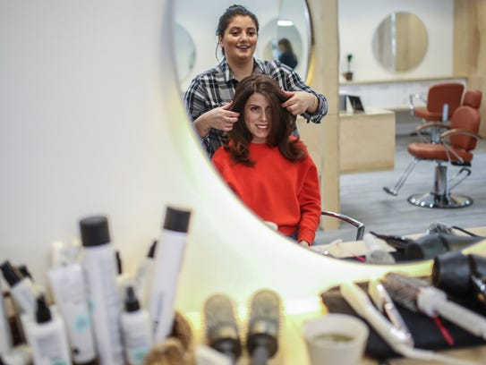 Katie Katz of Detroit gets a blowout from stylist Nina Nafal of Novi at the Detroit Blows.