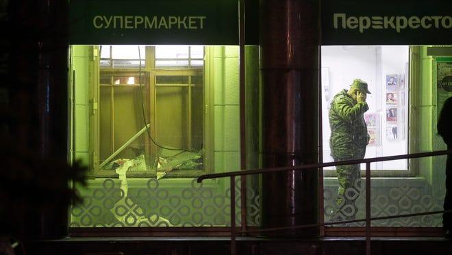 An investigator speaks on the phone inside a supermarket, after an explosion in St.Petersburg, Russia, Wednesday, Dec. 27, 2017. Russian officials say at least 10 people have been injured by an explosion at a supermarket in St. Petersburg.