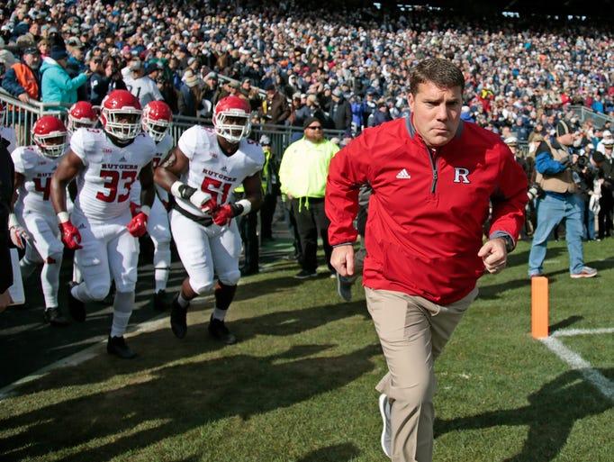 Rutgers head coach Chris Ash, leads his team onto the