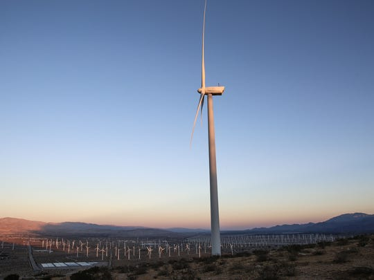 Wind turbines spin and generate electricity just west