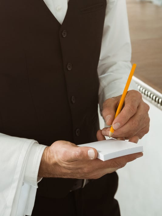 Portrait of waiter holding notepad and pen